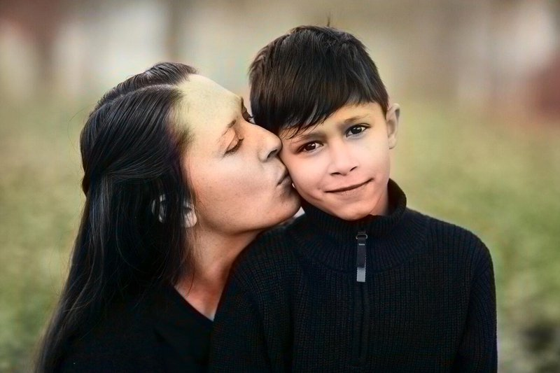 Colorized enhance image of mother kissing her son on the cheek in a forest with realistic skintones and blackground color