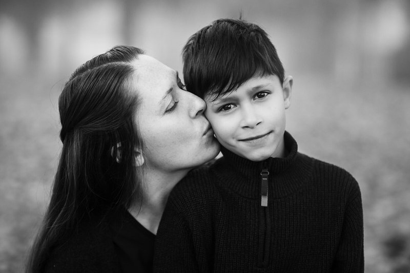 black and white image of mother kissing her son on the cheek in a forest