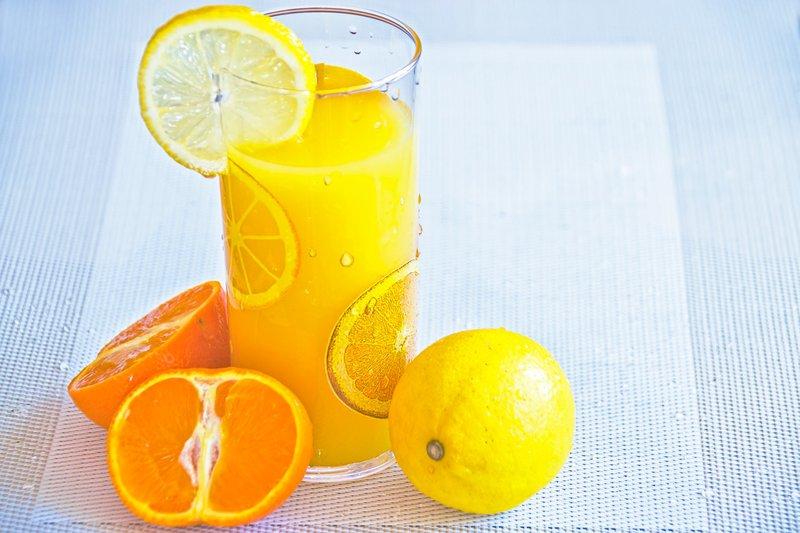 A glass of orange juice garnished with orange and lemon slices.
