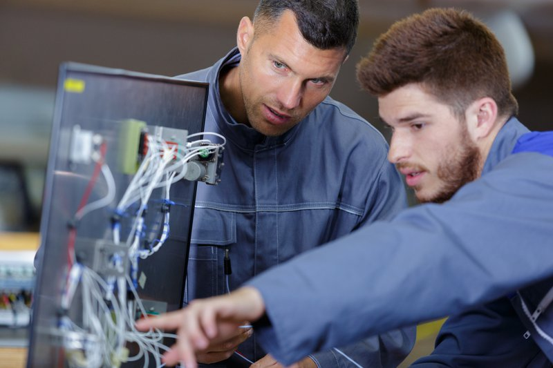 apprentice electrician asking tutor about wiring