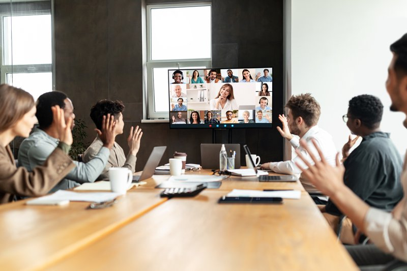Distant Virtual Meeting Concept. Diverse business people making online video call with colleagues, sitting at desk in boardroom, waving hands at tv screen at office, talking on web with remote workers