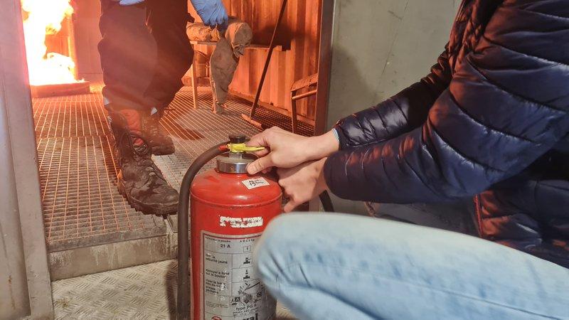 Een medewerker oefent een eerste bluspoging bij brand