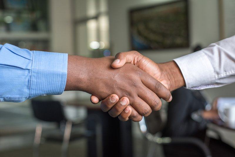 Two men who work at a startup, shaking hands