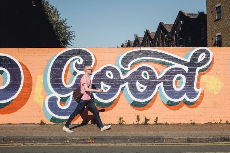"Man walking in front of ""GOOD"" graffiti"