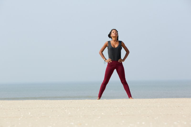 Portrait of an african woman doing yoga breathing exercise with hands on hip at the beach