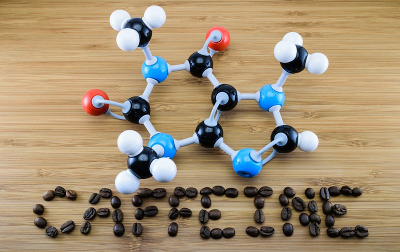 caffeine molecule structure (atomic model) with coffee bean align ìn word on wood background