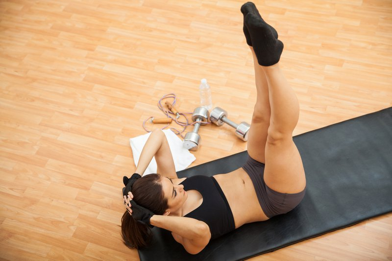 High angle view of a young woman in sporty outfit doing leg raises and crunches at the gym as part of her routine