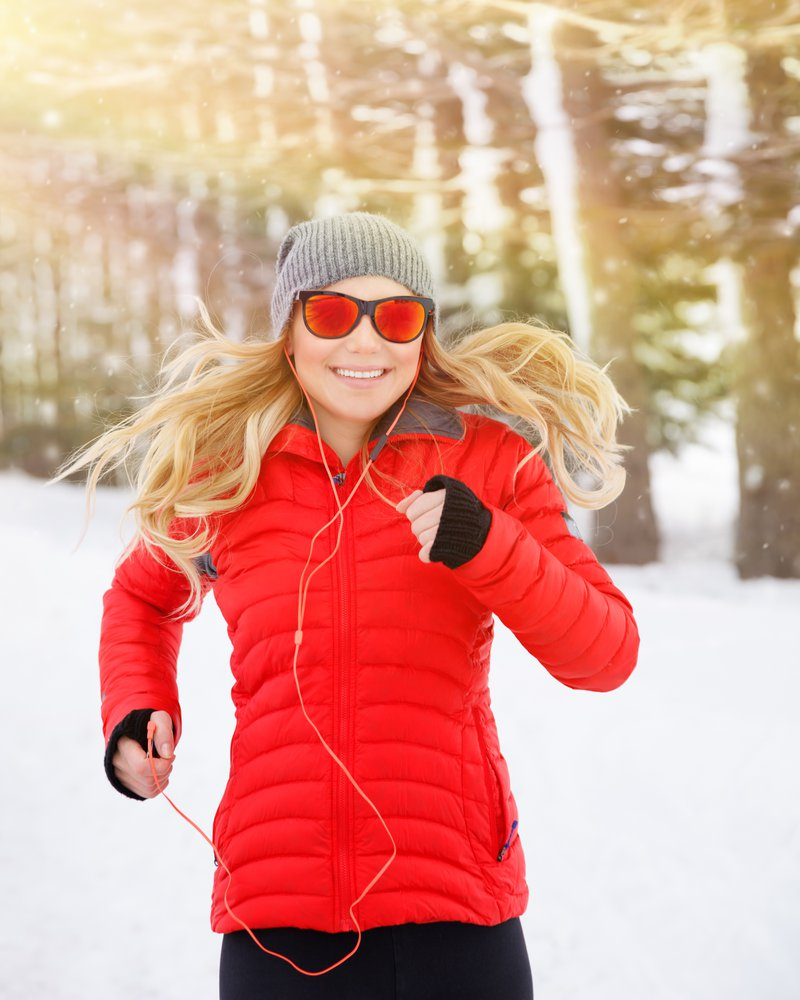 Portrait of beautiful happy runner outdoors, cute blond female running in the winter park and listening music in headphones, active and healthy lifestyle
