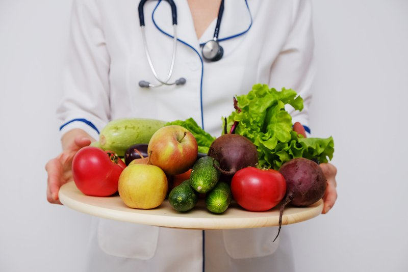 Nutritionist woman holding a plate with fruits and vegetables