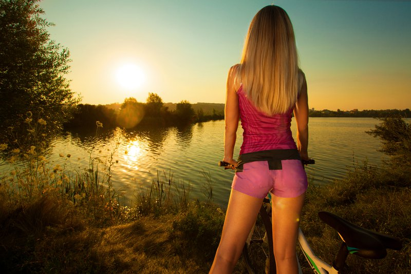 Close-up of rear view of a pretty woman on bicycle relaxing at Sunset. Active Leisure Concept. Healthy lifestyle.