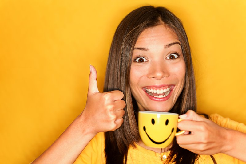 Woman drinking coffee happy giving thumbs up smiling enjoying her morning coffee on yellow background. Beautiful young multiracial Caucasian / Chinese Asian female model.