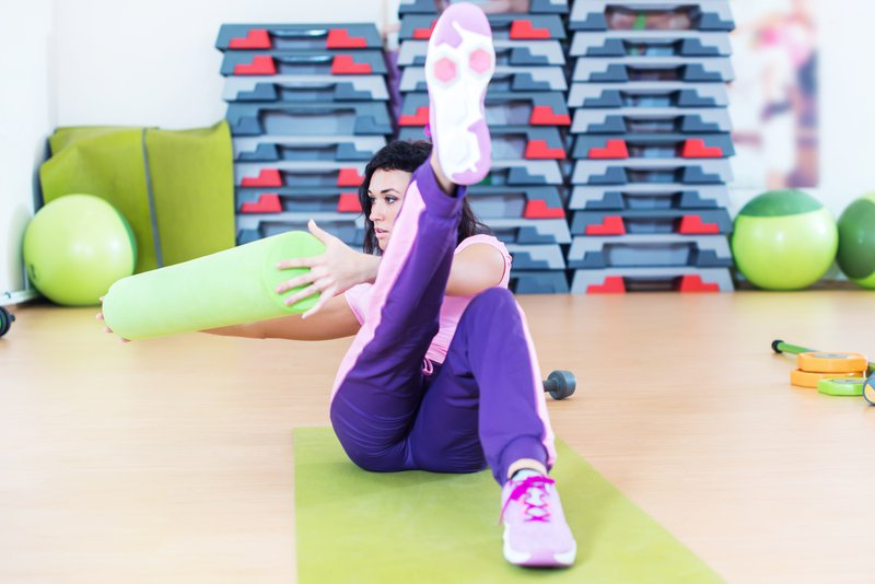 Fit woman doing abs workout exercise russian twists with raised leg.