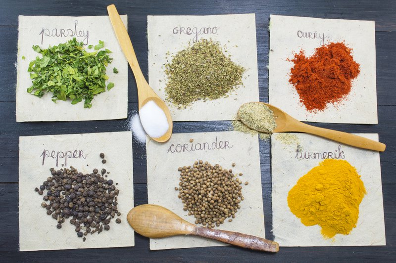 Various spices  on recycled papers with labels placed  on a dark wooden table