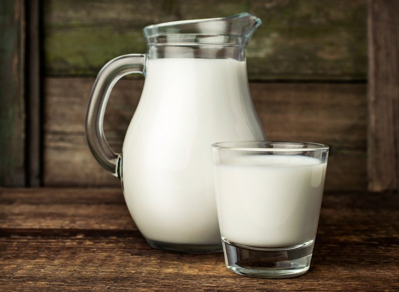 fresh milk in glass jug and glass on wooden background