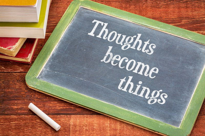 thoughts become things - law of attraction concept - inspirational text on a slate blackboard with a white chalk and a stack of books against rustic wooden table