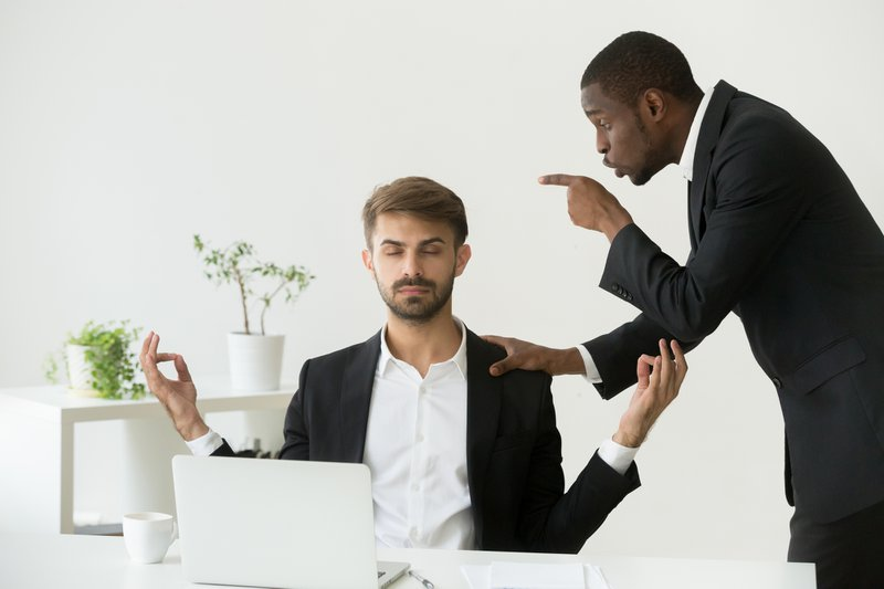 Caucasian employee meditating at workplace ignoring angry african boss scolding him, calm white office worker doing yoga exercises avoiding negativity stress at work, keeping mental emotional balance
