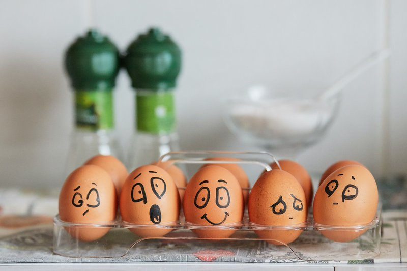 Painted eggs expressing a range of emotions from joy to depression.