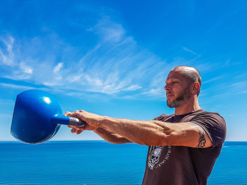 Man performs the kettlebell swing in front of the Mediterranean sea.