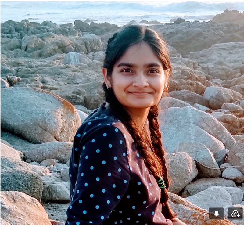 """alt=""""jyoti rani, a collegeadvisor.com student poses for the camera on a beach in a blue shirt with braids"""""""