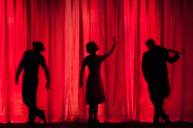 """alt=""""trio of high school theater students acting in an extracurricular production of """"Singing in the Rain"""""""""""