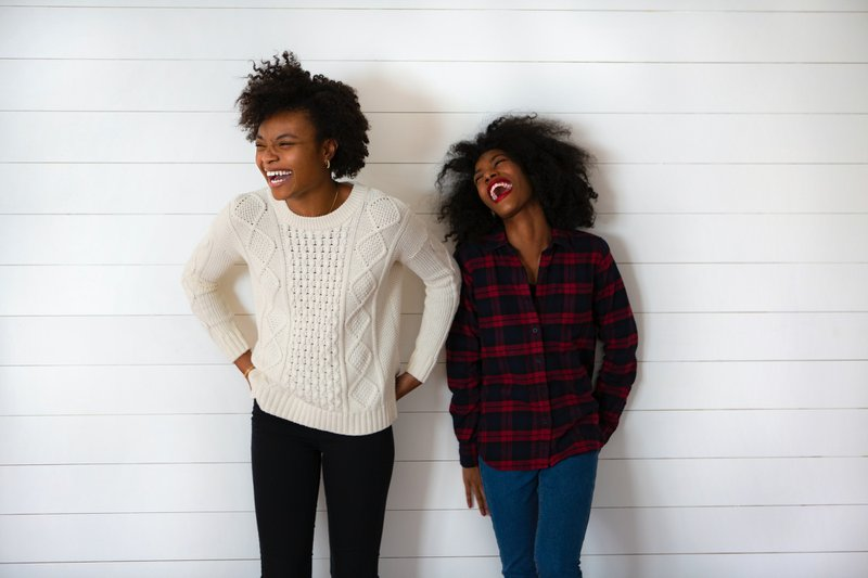 two black students smile and laugh at the camera, while standing against a white back drop