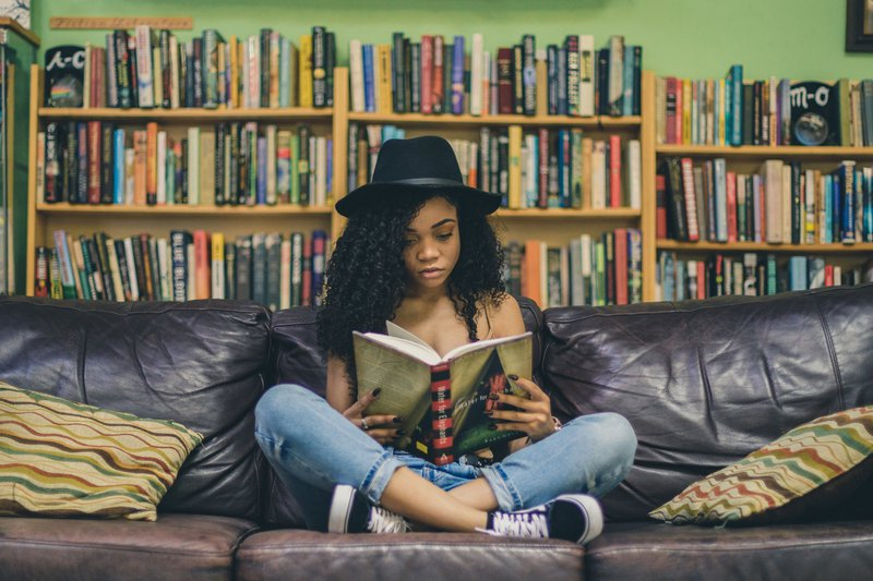 student reading a selection from a back-to-school reading list on a couch in front of a shelf full of books