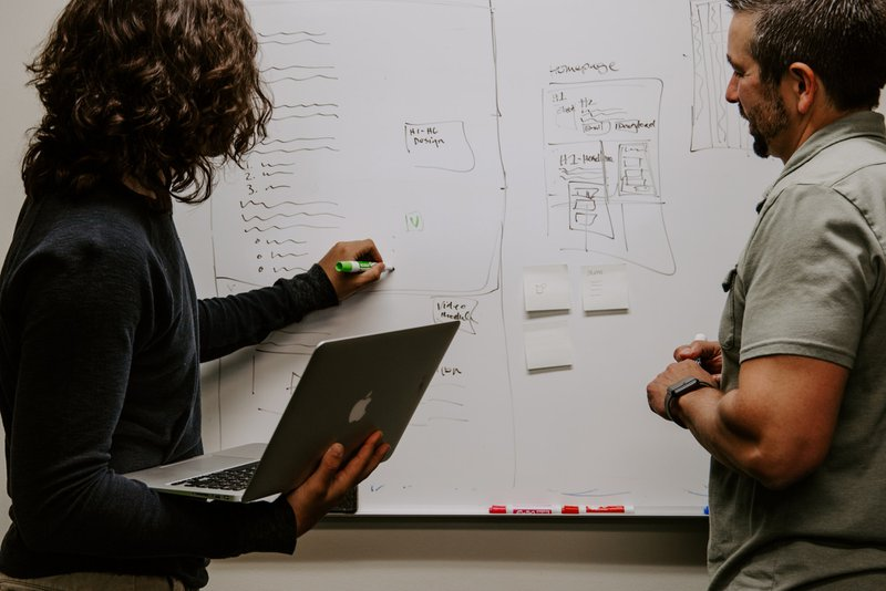 """alt=""""man and woman in public health field working on a white board. Woman is holding Macbook and writing with a green marker."""""""