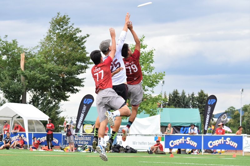 Men playing Ultimate Frisbee, jumping for the disc in the air.