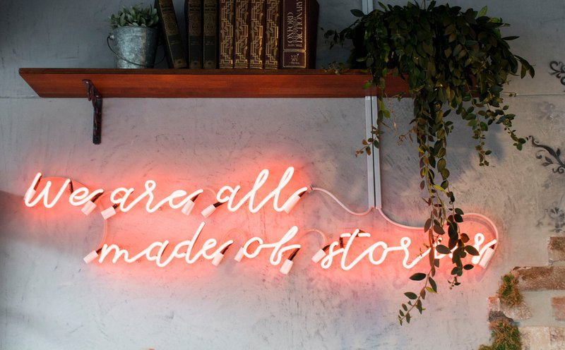 personal narrative photo is text we are all made of stories in neon under a bookshelf on the wall
