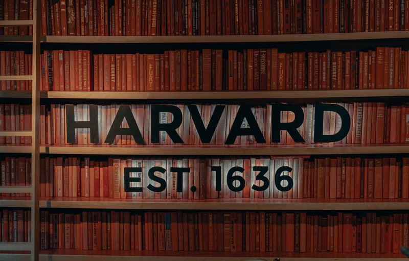 harvard supplemental essays guide photo of a bookcase filled with books and the words Harvard est. 1636 on the front