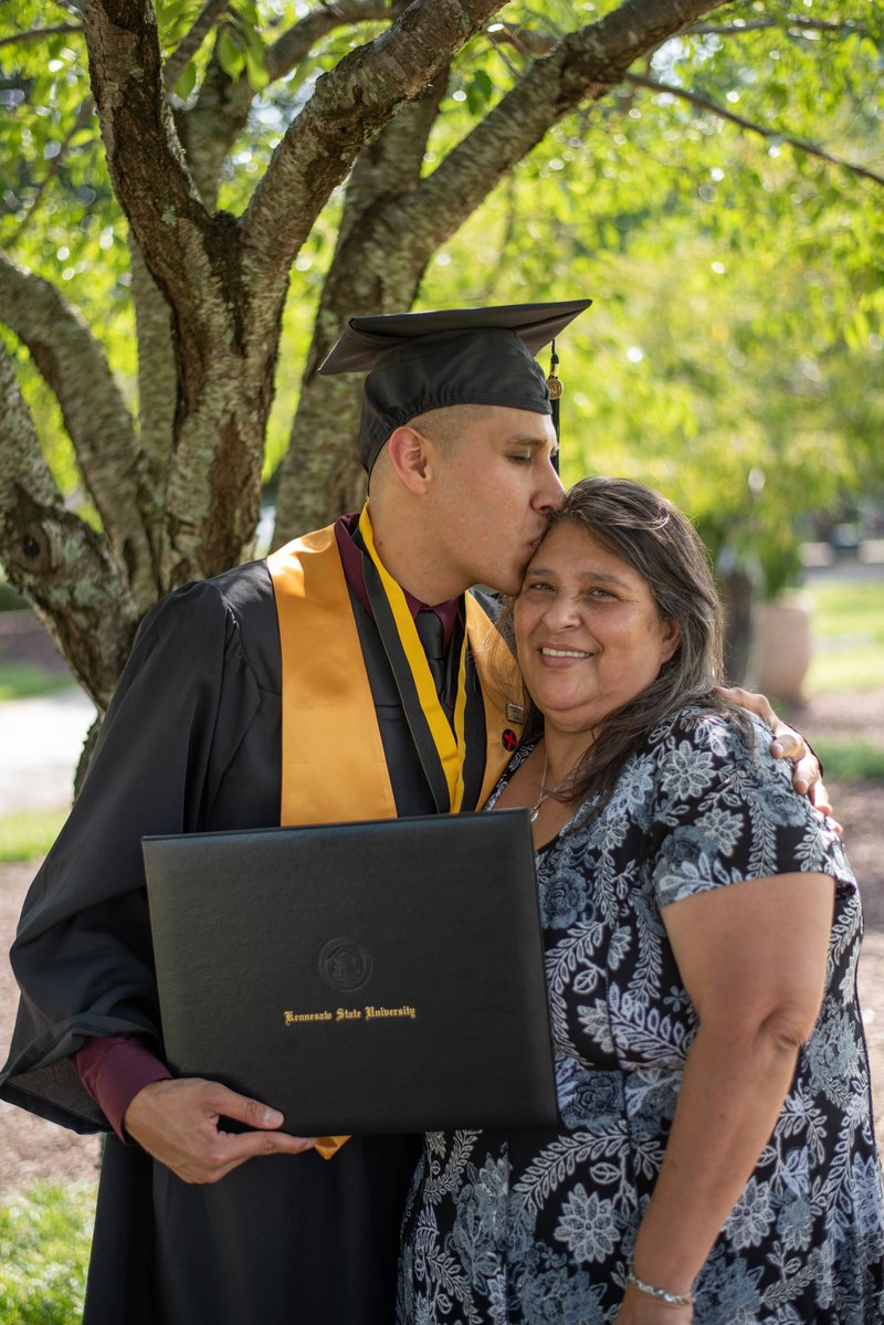 Helicopter parent holds takes picture with son at college graduation