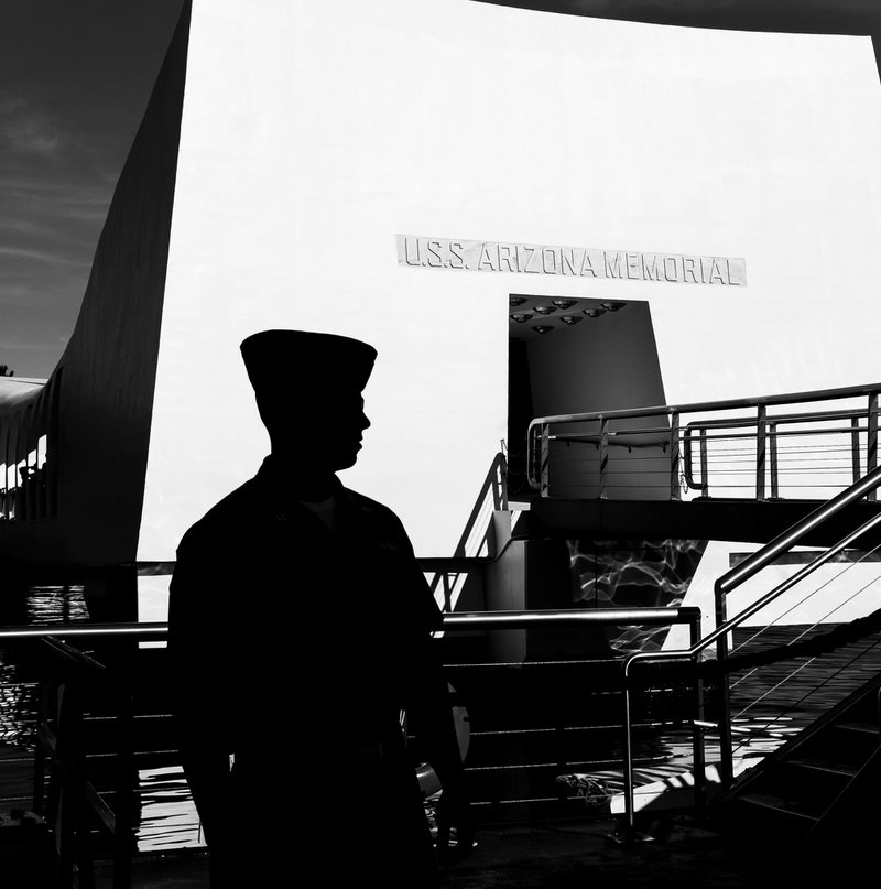 US Navy sailor at the USS Arizona Memorial in Pearl Harbor, Hawaii. I love the silhouette of the sailor against the stark white of the memorial. I was fortunate to capture his profile as he walked past.