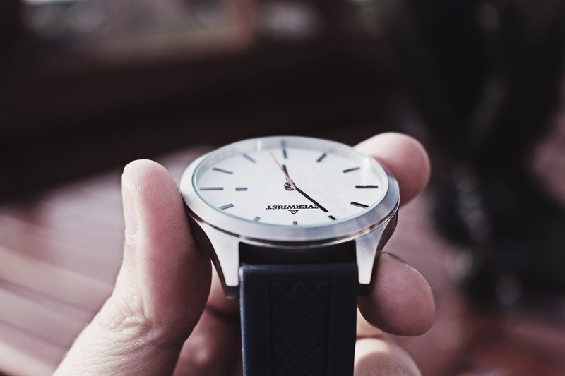 person holding silver-colored analog awtch with black strap