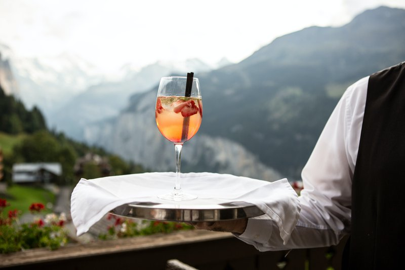 A waiter serving a glass of cocktail with a mountain view in the background
