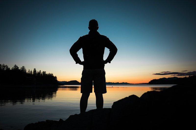 Male silhouette over a lake