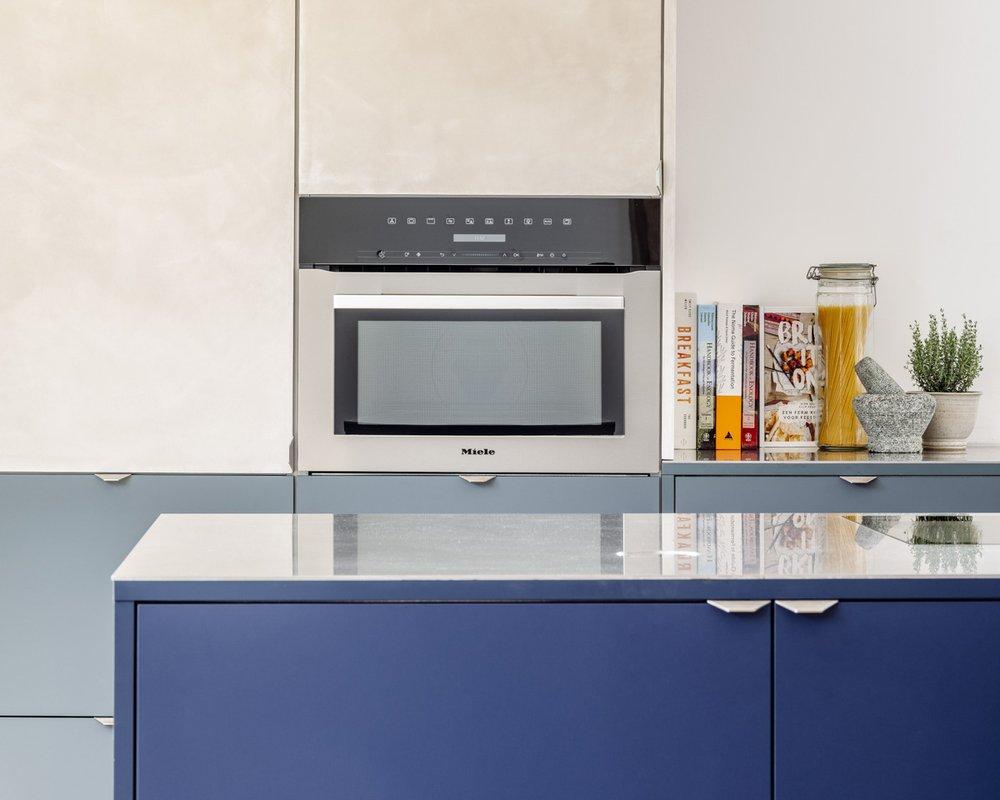 Keukenblok in Fenix blauw Fes kleur,  wandkast onderaan in Fenix Verde Comodoro en kolomkasten uitgevoerd in Natural Texture. Alles voorzien van het BL handvat. Samen helemaal Firmax.