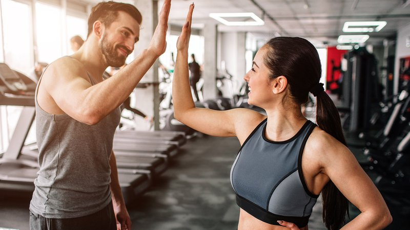 A beautiful girl and her well-built boyfriend are greeting each other with a high-five. They are happy to see each othr in the gym. Young people are ready to start their workout