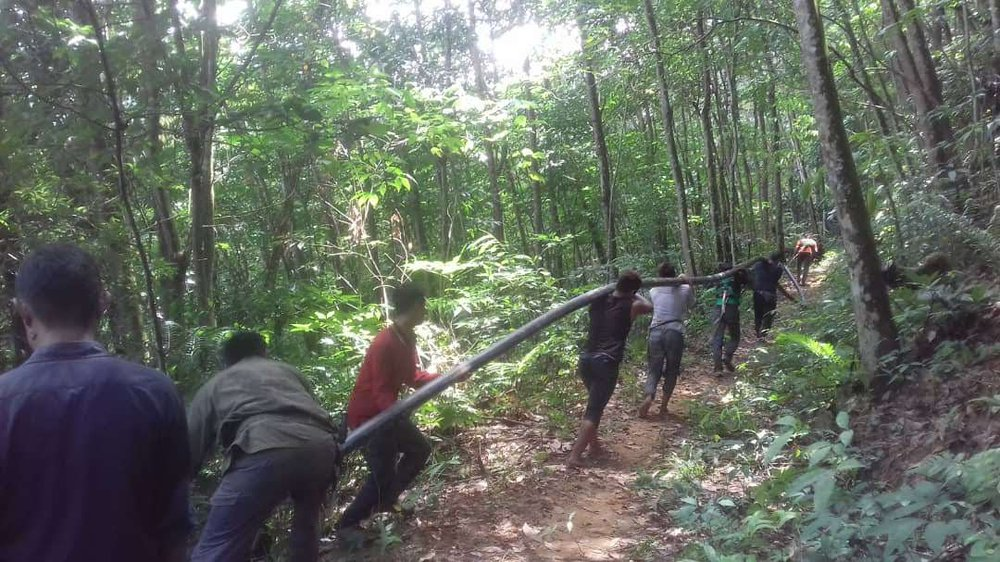Orang Asli villagers and volunteers carrying piping through the jungle