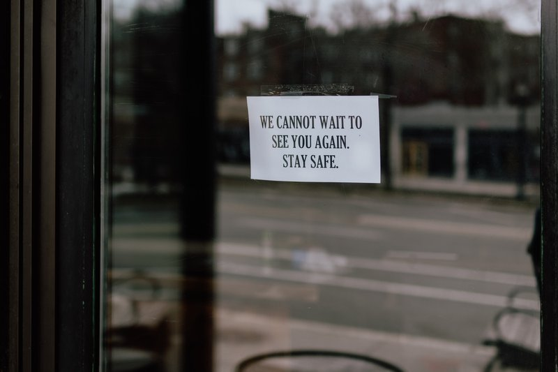 Sign on door of shuttered business. COVID-19 relief packages and tax credits