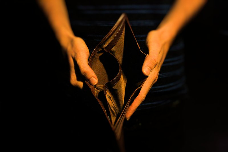 Image of two hands holidng an open empty wallet. This indicates that budgeting is an important skill of personal finances.