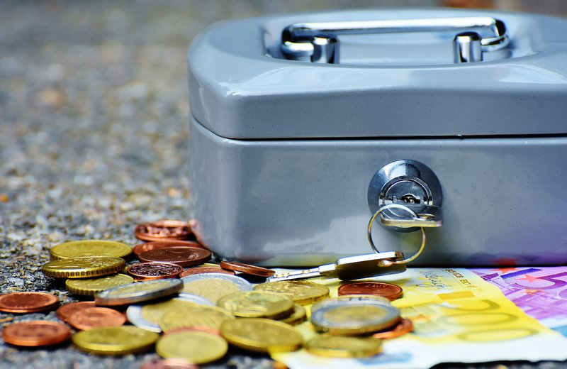 Image of a safe with a key in the lock and coins and cuurency lying around it. The image symbolizes saving for an emergency.
