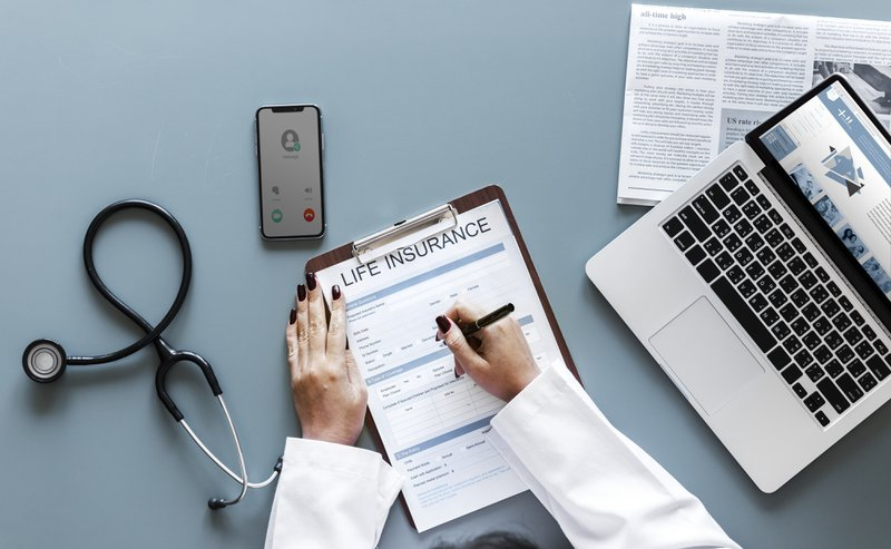 A doctor's desk showing the hands of a woman doctor filling a life insurance form. Phone, laptop, etc are on the desk.