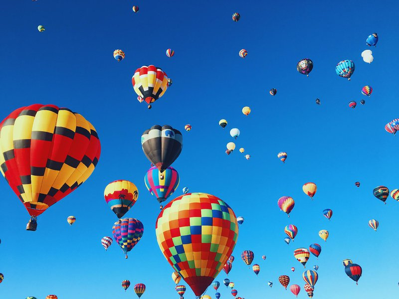 Image of parachutes floating in the blue sky.