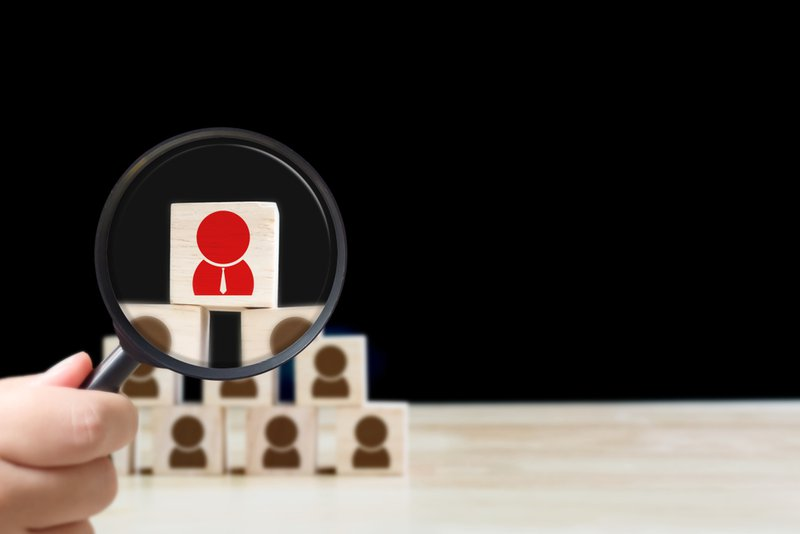 Blocks of wood with line drawings of human figures stacked in a pyramid. A magnifying glass hovers over one which is red and clear, while the rest are black and blurry. This indicates success in job search