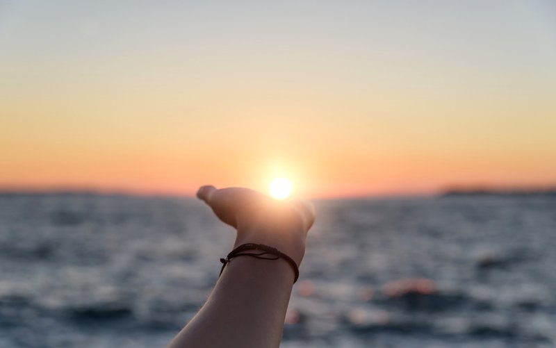 Hand reaching towards the sun at sunset against the background of the sea; picture indicates healing