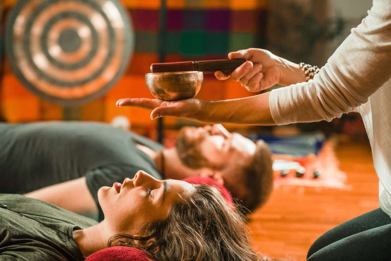 A man and woman lying down and being taken through a guided meditation session with a facilitator playing the Tibetan bowl.