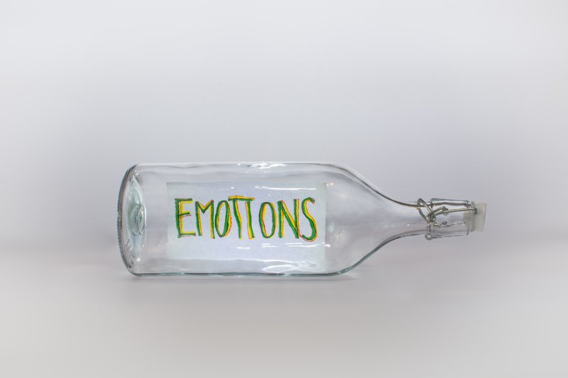 A glass bottle with the word emotions written on a label. The image indicates bottling up of emotions.