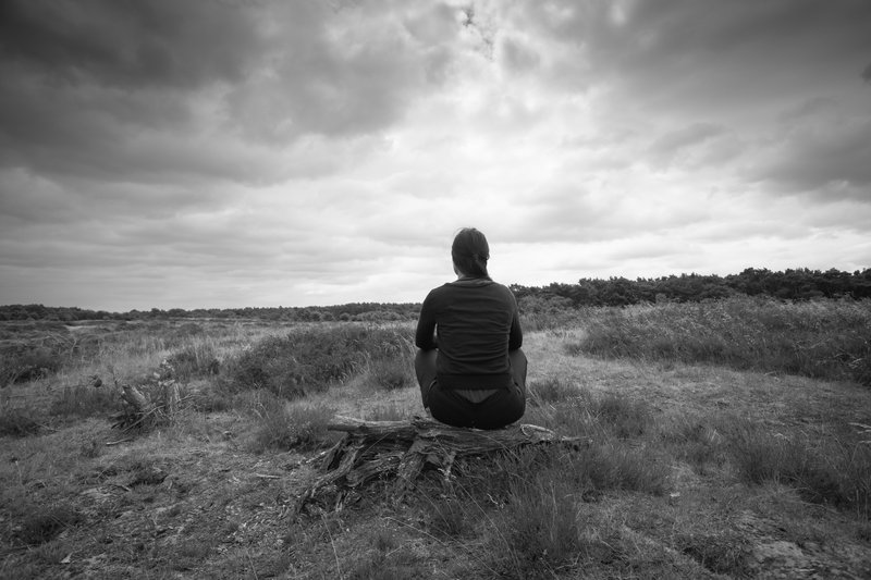 A girl sitting alone, forlorn outdoors in a meadow. The picture is black and white. It indicates she is going through one of the stages of grief.