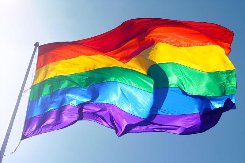 Rainbow flag, sun, wind, and blue sky