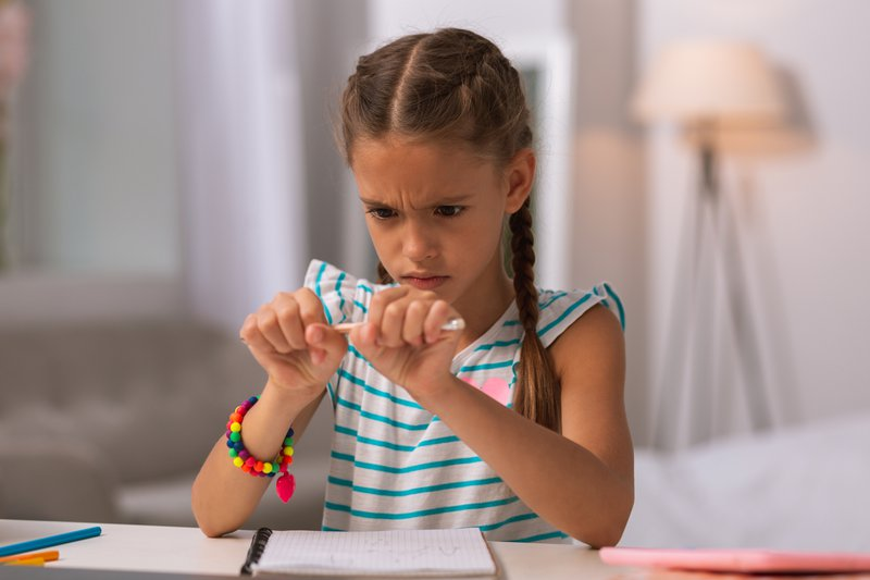 A young girl suppressing her emotion of anger and it manifesting as her wanting to break a pencil she is holding in both her hands. She is sitting at a desk with her notebook in front of her.